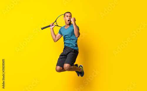 Foto Afro American tennis player man over isolated yellow background