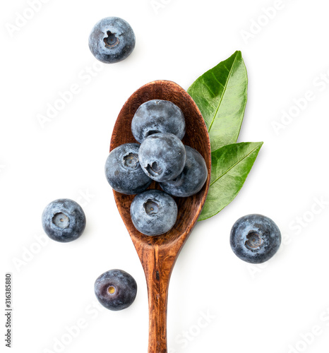 Obraz na plátně Blueberries and green leaves in a wooden spoon top view close-up