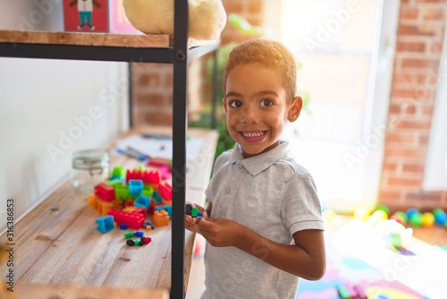 Obraz Beautiful african american toddler standing playing with small building blocks on shelving at kindergarten - fototapety do salonu