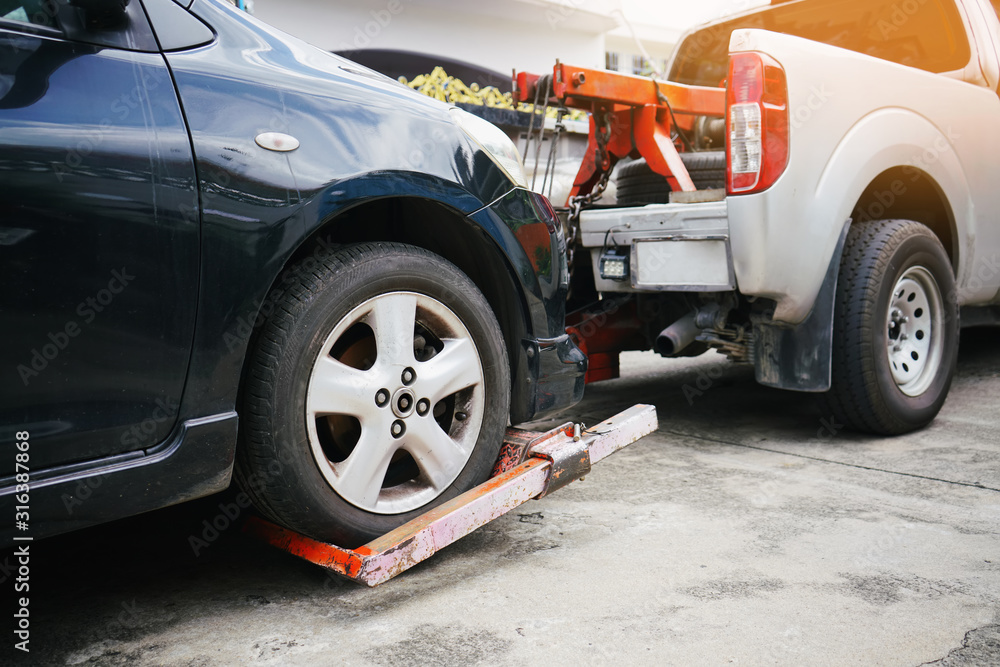 Fototapeta Tow truck picking up and towing old broken down car on a roadside