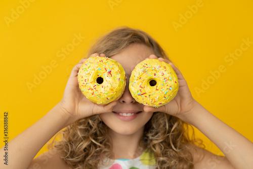 Fényképezés Happy child holding glazed donut