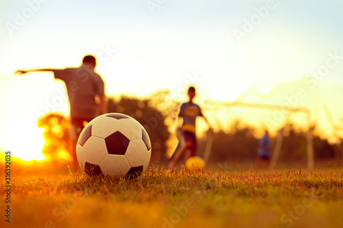 Action sport outdoors of kids having fun playing soccer football for exercise in community rural area under the twilight sunset sky Wallpaper Mural
