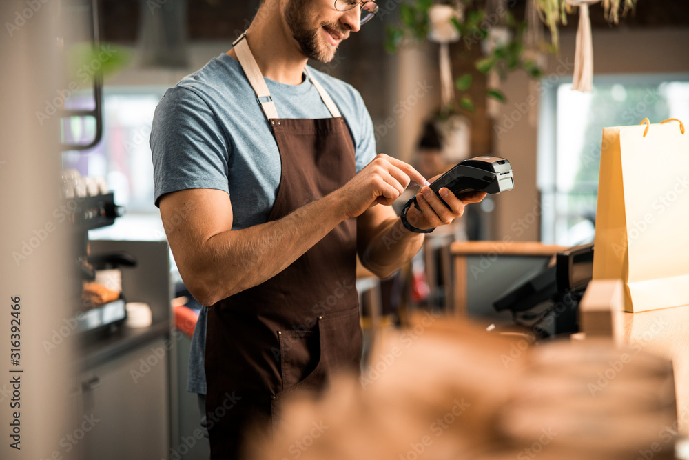 Fototapeta Happy male waiter in apron with card reader