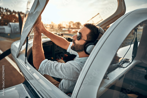 Canvas-taulu Portrait of cool young adult pilot sitting in private air plane ready to take off