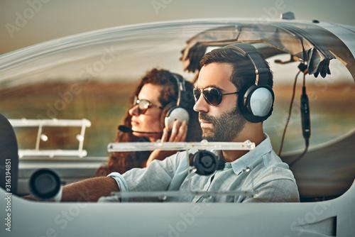 Fototapeta Young pilot and beautiful stewardess sitting together inside airplane cabin wait