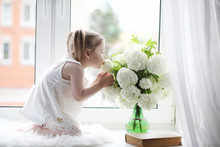 A Little Girl Is Sitting On The Windowsill. A Bouquet Of Flowers In A Vase By The Window And A Girl Sniffing Flowers. A Little Princess In A White Dress With A Bouquet Of White Flowers By The Window.