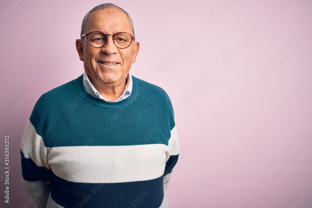 Fototapeta Senior handsome man wearing casual sweater and glasses over isolated pink background with a happy and cool smile on face. Lucky person.