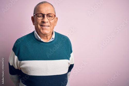 Obraz Senior handsome man wearing casual sweater and glasses over isolated pink background with a happy and cool smile on face. Lucky person. - fototapety do salonu