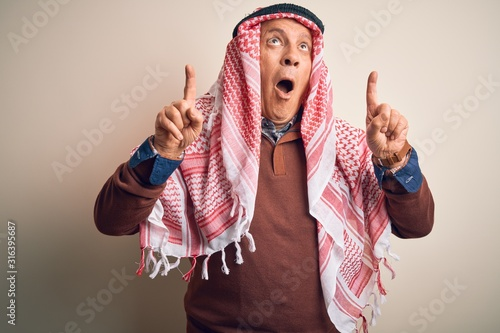 Senior handsome arab man wearing keffiyeh standing over isolated white background amazed and surprised looking up and pointing with fingers and raised arms Canvas Print