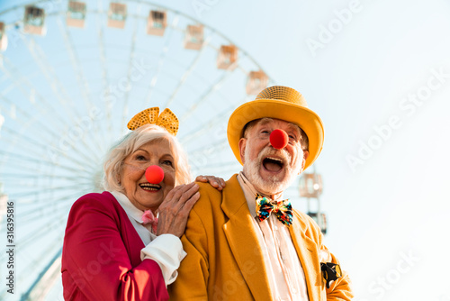 Fototapeta Cheerful mature couple having fun while walking in an amusement park obraz