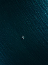 Aerial View Of Wooden Fishing Boat In Deep Blue Sea.