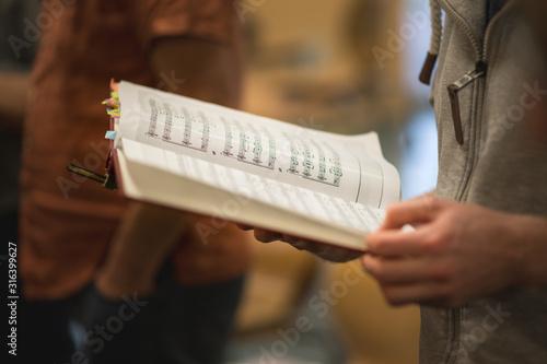 Fotografiet Hand hält Noten bei Chorprobe und blättert, geringe schärfentiefe