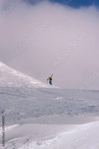 Skier climbing a mountain on foot while carrying his skies ready for some off-piste Wallpaper Mural