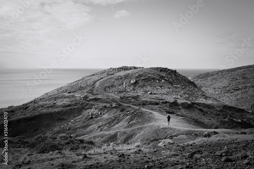 An adventurer is walking in desertic place near the Atlantic Ocean (Madeira, Por Canvas Print