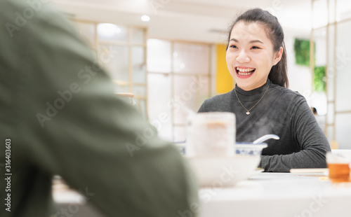Young asian woman talking face to face in restaurant Canvas Print