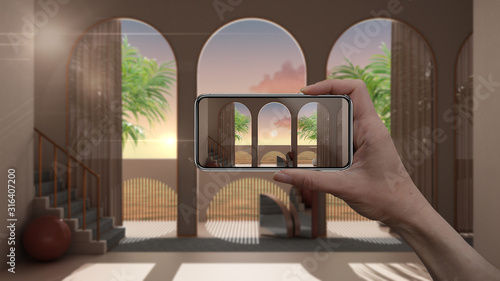 Fototapeta Hand holding smart phone, AR application, simulate furniture and interior design products in real home, architect designer concept, blur background, dreamy terrace, sea panorama obraz