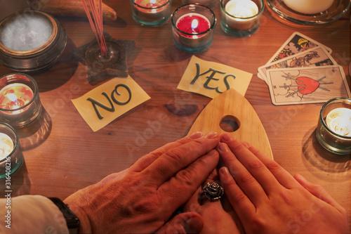 Fotografie, Obraz Geisterbefragung von drei Menschen mit Hilfe eine Ouija Bretts bei Kerzenschein