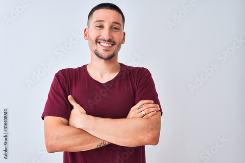 Young handsome man standing over isolated background happy face smiling with crossed arms looking at the camera Obraz na płótnie