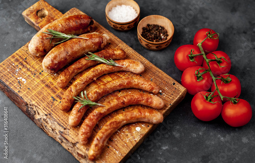Fototapeta Various grilled sausages with spices on a stone table with copy space for your text. obraz