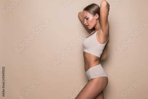 Young sexy woman with perfect body in underwear standing on beige background Canvas Print