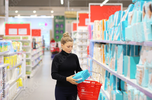 woman shopping in supermarket reading product information Fototapet