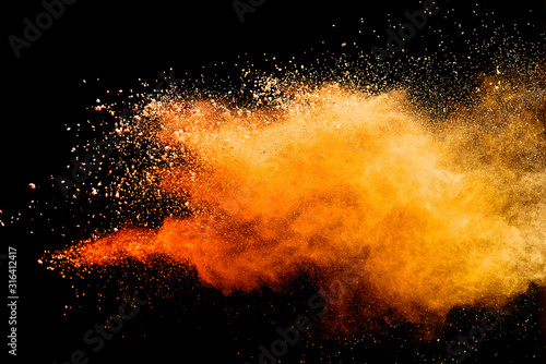 Abstract orange powder explosion isolated on black background. - 316412417