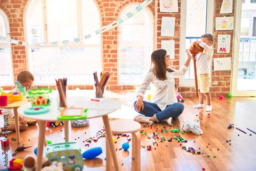 Fototapeta Beautiful teacher and toddlers playing around lots of toys at kindergarten obraz na płótnie