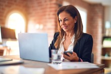 Middle Age Beautiful Businesswoman Smiling Happy And Confident. Sitting On Chair Working In A Desk Using Smartphone At The Office