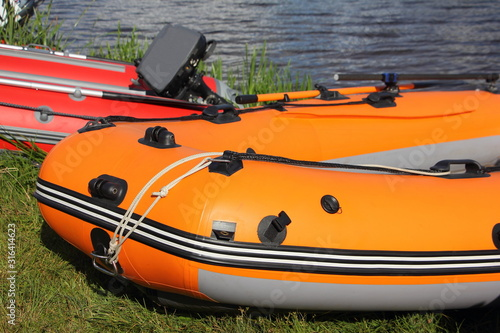 Fotografering Close up orange and red inflatable motor boats near the shore against the backgr