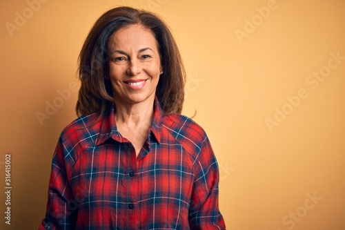 Fotografía Middle age beautiful woman wearing casual shirt standing over isolated yellow background with a happy and cool smile on face