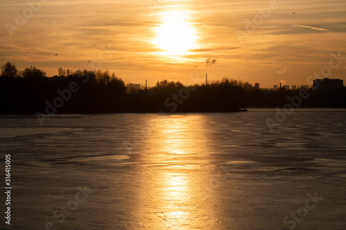 Winter sunset on the background of a frozen pond, lake. Moscow. Russia.