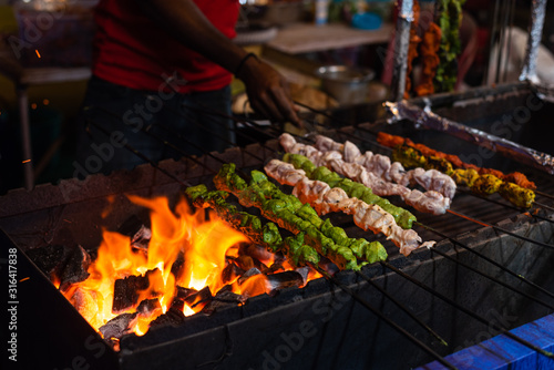 Street food/Traditional Grilled tandoori of assorted meats with charcoal and fire on skewers