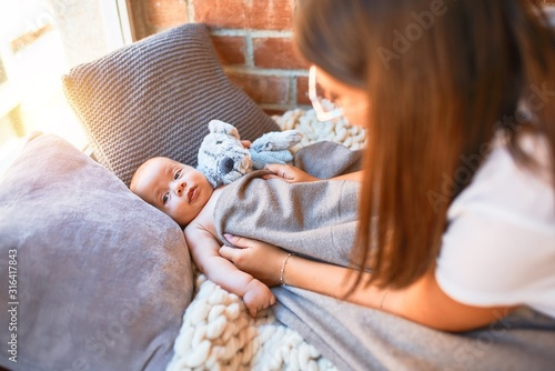 Obraz Young beautifull woman and her baby on the floor over blanket at home. Newborn and mother relaxing and resting comfortable with doll - fototapety do salonu