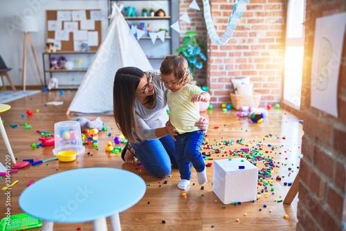 Obraz Young beautiful teacher and toddler playing at kindergarten - fototapety do salonu