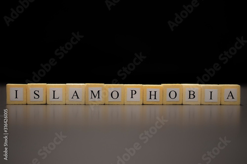 ISLAMOPHOBIA written on wooden cubes isolated on a black background Canvas Print