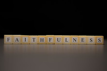 The Word FAITHFULNESS Written On Wooden Cubes Isolated On A Black Background..