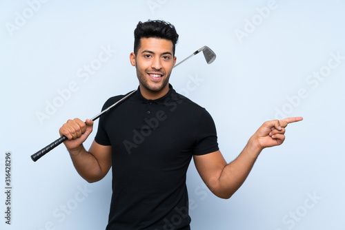 Fototapeta Handsome young man playing golf over isolated blue background surprised and pointing finger to the side obraz