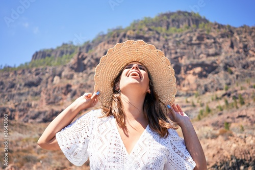 Young beautiful woman enjoying summer vacation on mountain landscape, traveler girl sunbathing with open arms