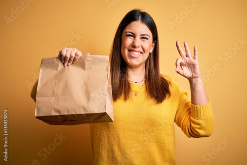 Young beautiful woman holding take away paper bag from delivery over yellow back Fototapete