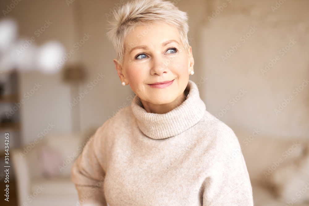 Fototapeta People, age and maturity. Close up shot of elegant blonde middle aged woman with short haircut looking up with pensive smile, thinking about something pleasant, making plans, recollecting old days