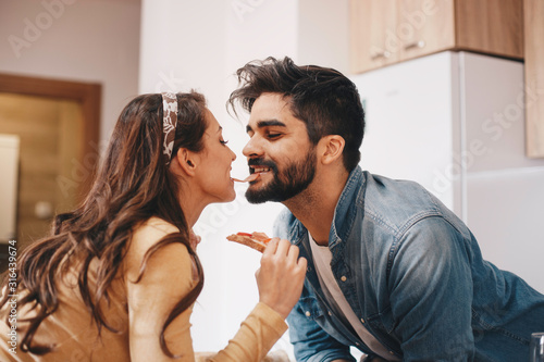 A goofy couple sharing a slice of ham with their mouth in the kitchen Canvas Print