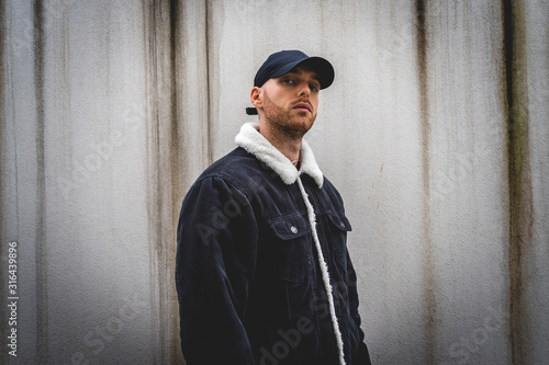Fototapeta portrait of young rapper posing in front of a white wall obraz