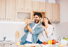 A Young Couple Fooling Around - Singing, While Making A Meal.
