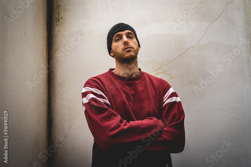 portrait of young rapper posing in front of a white wall Canvas Print