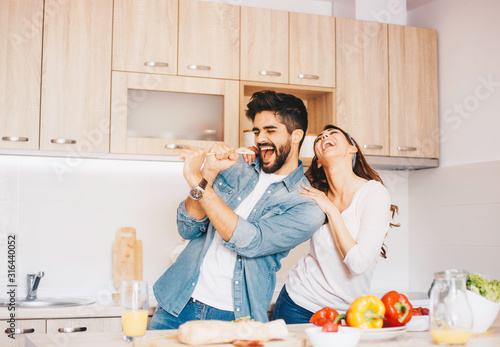 A young couple fooling around - singing, while making a meal. фототапет