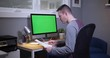 A man sits at a desk in his home office and pays bills on his computer. Green screen on PC for custom screen content.