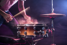 The Drummer Plays The Drums. Beautiful Blue And Red Background, With Rays Of Light. Beautiful Special Effects Smoke And Lighting. The Process Of Playing A Musical Instrument.