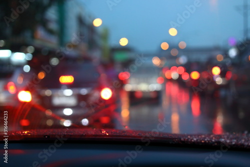 mata magnetyczna traffic jam on night road city with storm rainy day weather, car driving on street town with water rain drop on windshield outside of bad view