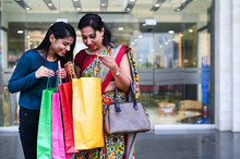 Mother And Adult Daughter Posing Together Outside The Shopping Mall After Shopping For Festive Season With Colorful Shopping Bags In Hand.