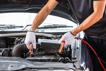 Close Up Of Man Hand Charging A Car Battery Using Electricity Trough Jumper Cables.